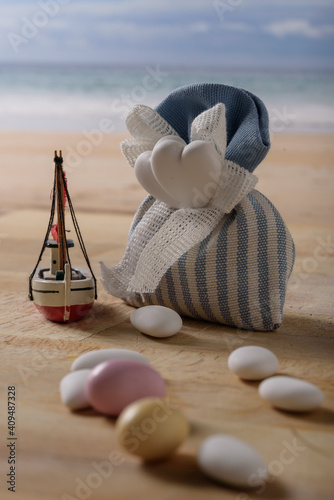 sweet food and a boat at  the seaside. composition with sweet almonds and a boat at the seaside. italian food to celebrate wedding and newborn. copy space in the middle © marinzolich