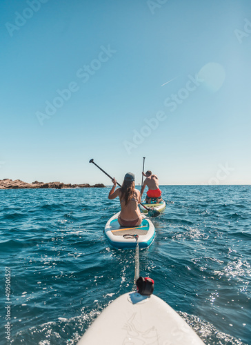 Fototapeta A group of people paddle with SUP stand up paddle boards on a hot day in the Adr