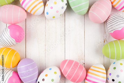 Colorful Easter Egg frame. Top down view against a white wood background. Copy space. © Jenifoto