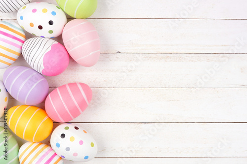 Colorful Easter Egg side border. Above view against a white wood background. Copy space. © Jenifoto