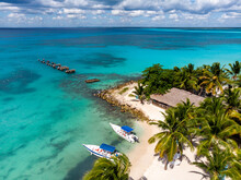 Aerial Drone View Of The Paradise Beach With Old Broken Pier, Boats, Palm Trees And Blue Water Of Caribbean Sea With Transparent Coral Bottom, Saona Island, Dominican Republic