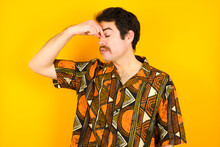 Very Upset, Young Caucasian Man Wearing Printed Shirt Against Yellow Wall Touching Nose Between Closed Eyes, Wants To Cry, Having Stressful Relationship Or Having Troubles With Work