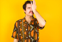 Frustrated Young Caucasian Man Wearing Printed Shirt Against Yellow Wall Holding Hand On Forehead Being Depressed Regretting What He Did Having Headache, Looking Stressful.