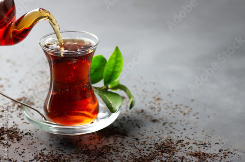 Glass cup of black tea pouring from teapot with fresh tea leaves, traditional turkish brewed hot drink © mescioglu