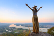 Asian Woman Enjoying High Angle View Of Mekong River With Open Hands Standing On The Cliff In Nongkhai, Thailand