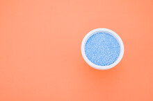 Top View Of Blue Sand In A Small Cup Isolated On An Orange Background