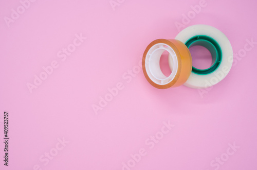 Obraz na plátně Top view of two rolls of sticky tapes isolated on a pink background
