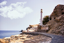 Crete, Greece - Wide Angle Shot Of A Rocky Path Against A White Light House Situated On A Hill In A Center Of Island