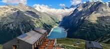 The Olperer Hut With Views Of Alpine Lake Schlegeis In The Valley Zillertal, Austrian Alps