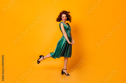 Obraz Excited fit girl in green dress standing on one leg. Full length view of graceful lady dancing on yellow background. - fototapety do salonu
