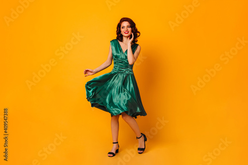 Obraz Charming woman in green dress smiling and looking away. Full length view of gorgeous curly girl dancing on yellow background. - fototapety do salonu