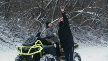 Young Couple Posing With ATV Quad Bike In Winter Forest. Young Man With A Red Hat Takes Selfie With His Girlfriend On Atv