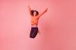 Active girl in orange hoodie and dark leggings vigorously jumping on pink background