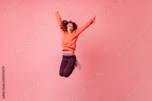 Obraz Active girl in orange hoodie and dark leggings vigorously jumping on pink background - fototapety do salonu