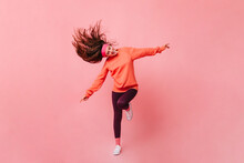 Young Lady In Sports Outfit Dancing On Pink Background. Full Length Portrait Of Woman In Orange Sweatshirt
