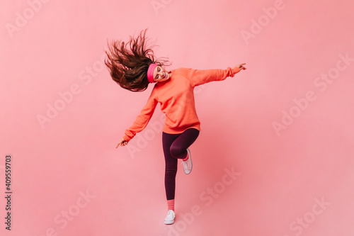 Obraz Young lady in sports outfit dancing on pink background. Full length portrait of woman in orange sweatshirt - fototapety do salonu