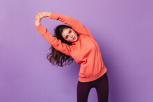 Portrait Of Curly Brunette Girl Doing Exercises On Purple Background. Lady In Bright Hoodie And Leggings Is Engaged In Fitness