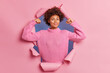 Leinwandbild Motiv Self assured beautiful young Afro American woman raises arms shows biceps being strong and powerful proud of her own achievements wears casual knitted sweater breaks through paper background