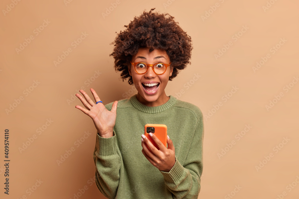 Fototapeta Overjoyed excited woman with Afro hair raises palm has eyes full of happiness after receiving excellent news holds mobile phone wears spectacles and optical glasses isolated over brown wall.