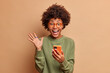 Leinwandbild Motiv Overjoyed excited woman with Afro hair raises palm has eyes full of happiness after receiving excellent news holds mobile phone wears spectacles and optical glasses isolated over brown wall.