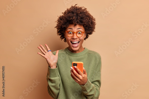 Overjoyed excited woman with Afro hair raises palm has eyes full of happiness after receiving excellent news holds mobile phone wears spectacles and optical glasses isolated over brown wall.