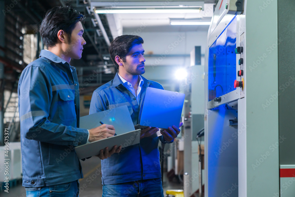 Fototapeta Male Asian caucasian engineer professional having a discussion standing consult at machine in the factory ,two expert coworker brainstorm explaining and solves the process of the cnc operate machine
