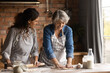 Leinwandbild Motiv Happy mature grey haired woman with grownup daughter wearing aprons cooking handmade pastry, rolling dough, chatting, having fun, standing in kitchen at home, family spending leisure time together