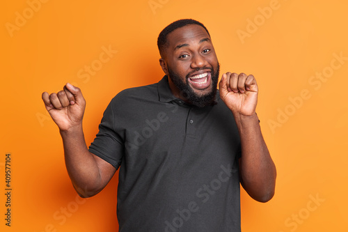 Studio shot of carefree positive black man with thick beard dances carefree has upbeat mood raises arms enjoys favorite music isolated over vivid orange wall. Afro American guy moves actively indoor © Wayhome Studio