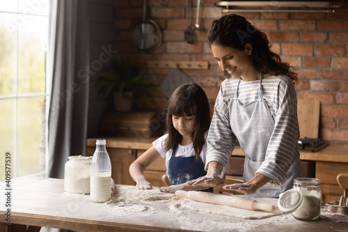 Fotografie, Obraz Smiling mother with little daughter kneading, rolling dough, cooking handmade pa