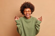 Glad dark skinned woman raises hands has carefree cheerful expression closes eyes smiles toothily wears optical glasses and sweater isolated over beige background. Happiness and joy concept.