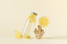 Bottle Of Infused Water With Ginger And Lemon Over Light Yellow Background.