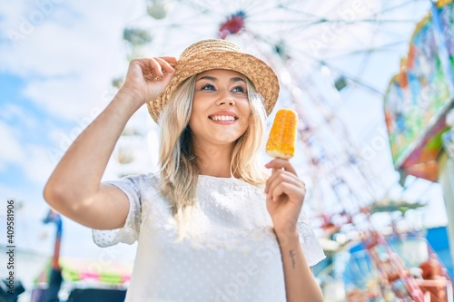 Fotografie, Tablou Young caucasian tourist girl smiling happy and eating ice cream at fairground
