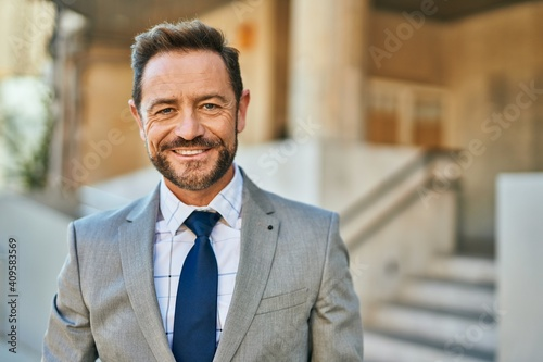 Middle age businessman smiling happy standing at the city.