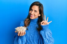 Young Latin Woman Holding Bowl With Pumpkin Seeds Doing Ok Sign With Fingers, Smiling Friendly Gesturing Excellent Symbol