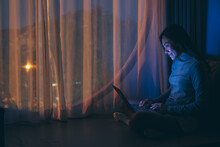 A Beautiful Young Woman Using And Working On Laptop Computer With Bright Light Screen In The Late Night At Home