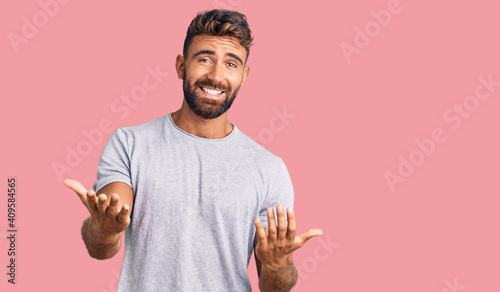 Obraz Young hispanic man wearing casual clothes smiling cheerful with open arms as friendly welcome, positive and confident greetings - fototapety do salonu