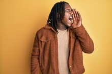 African American Man With Braids Wearing Brown Retro Jacket Shouting And Screaming Loud To Side With Hand On Mouth. Communication Concept.