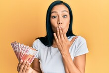 Beautiful Hispanic Woman Holding 100 Norwegian Krone Banknotes Covering Mouth With Hand, Shocked And Afraid For Mistake. Surprised Expression