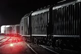 Large cargo train with goods leaving the terminal at night, wagons (containers) close-up. Concept urban scene. Illumination, red light. Freight transportation, industry, business, logistics, delivery
