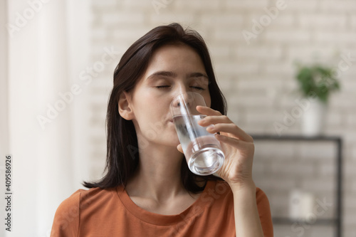 Fotografie, Obraz Close up thirsty attractive young woman enjoying cold fresh mineral water, beaut
