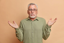 Uncertain Puzzled Grey Haired Mature Bearded Man Shrugs Shoulders With Hesitation Wears Spectacles And Shirt Poses Against Brown Background Says I Dont Care. Human Perception And Doubts Concept