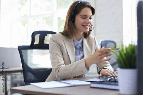 Fototapeta Beautiful smiling call center worker in headphones is working at modern office