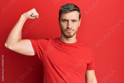 Obraz Handsome caucasian man wearing casual red tshirt strong person showing arm muscle, confident and proud of power - fototapety do salonu