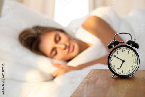 Photo Beautiful young woman sleeping and smiling while lying in bed comfortably and blissfully on the background of alarm clock is going to ring