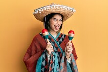 Young Caucasian Woman Holding Mexican Hat Using Maracas Sticking Tongue Out Happy With Funny Expression.