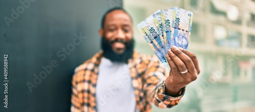 Handsome modern african american man with beard smiling positive standing at the street showing 100 south african rands banknotes - fototapety na wymiar