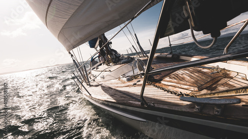 Sloop rigged modern yacht with wooden teak deck racing through the waves Fotobehang