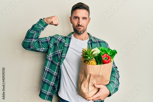 Obraz Handsome man with beard holding paper bag with groceries strong person showing arm muscle, confident and proud of power - fototapety do salonu