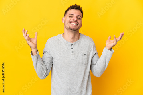 Fototapeta Young caucasian handsome man isolated on yellow background smiling a lot