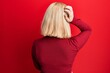 Leinwandbild Motiv Young blonde woman wearing casual clothes backwards thinking about doubt with hand on head